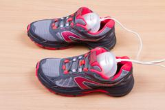 Electric ultraviolet shoe dryer and Sneakers. Stock Photos