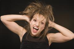 young silly crazy girl with messed hair making stupid faces on black background - stock photo