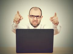 Angry  businessman sitting at his desk and screaming - stock photo