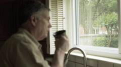 Rack focus to man standing next to a window drinking coffee 4k Stock Footage