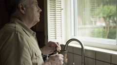 Man standing in his kitchen drinking coffee and eating a biscotti 4k Stock Footage