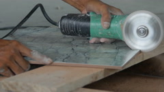 Worker cutting a tile using an angle grinder at construction site Stock Footage