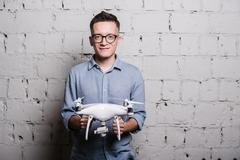 Young stylish Man in glasses holding the quadcopter drone DJI Phantom 4 on a - stock photo