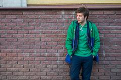 Common young man wearing green t-shirt jacket and jeans against a red brick wall Stock Photos
