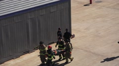 FIREMEN CARRYING LITTER WITH VICTIM ,MOCK DISASTER , Stock Footage