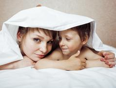 Young blond woman with little boy in bed, mother and son, happy family Kuvituskuvat