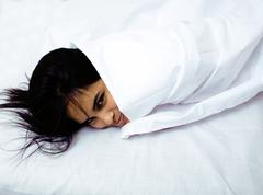 pretty indian brunette real woman in bed smiling, white sheets, tann skin close - stock photo