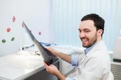 Young caucasian man doctor examines MRI image of human head in office looking at - stock photo