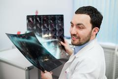 Hospital doctor holding patient's x-ray film and mri, looking away smiling Stock Photos