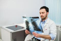 Health and mood. Serious Doctor talking to patient keeps chest X-ray in hands - stock photo
