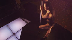 Top view woman dancer performs pole dance on dancing night club lighted stage Stock Footage