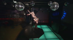 Sexy woman poledancer performs pole dance on nightclub stage in party lights Stock Footage