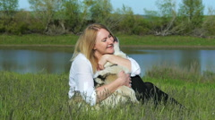 Pretty girl plays with a dog on the grass by the lake nature animals pets friend - stock footage