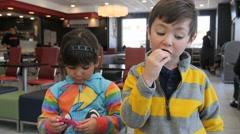 2 CUTE HISPANIC SIBLINGS EAT IN FAST FOOD RESTAURANT. - stock footage