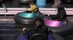 3 CUTE HISPANIC SIBLINGS RIDE BUMPER CARS AT AMUSEMENT PARK. - stock footage