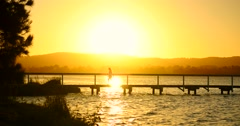 Young woman walks along pier at sunset Stock Footage