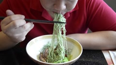 Chubby Asian male  eat  Hong Kong  jade noodle served with  roasted duck Stock Footage