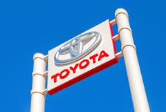Toyota automobile dealership sign against the blue sky background - stock photo
