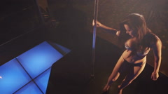 Top view of young sexy woman dancer performs pole dance on nightclub stage Stock Footage