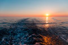 Sea sunset with ship trace - stock photo