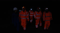 4K Team of workers at fuel plant come up from underground & walk into daylight - stock footage