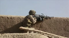 War in Afghanistan - United States Marine firing over clay wall Stock Footage