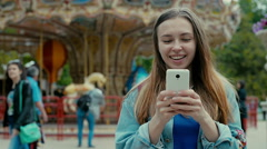 Girl with the phone against the backdrop of a theme park Stock Footage