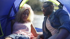 4K Attractive hipster couple chatting in their tent on camping trip - stock footage