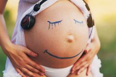 Pregnant woman belly closeup with smile funny face Stock Photos