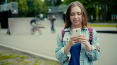 Girl with the phone against the backdrop of roller Park - stock footage