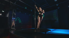 Young woman pole dancer dancing on lighted stage at dance night club - stock footage