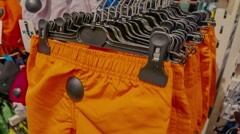 Bright orange shorts on the rack in the boutique Stock Footage