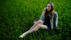 Young beautiful woman sitting on grass in summer city park and talking on cell - stock footage