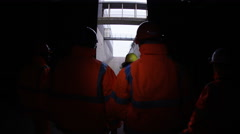 4K Workers at a fuel plant walking out into daylight after being underground - stock footage