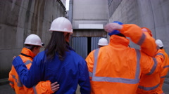 4K Workers at a fuel plant walking into darkness & preparing to go underground - stock footage