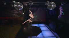 Woman poledancer performs pole dance on nightclub party lighted stage floor - stock footage