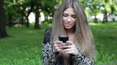 Young blonde woman is writing a message to somebody in the city park, smiling Stock Footage