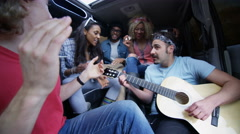 4K Happy hipster friends singing & playing guitar on road trip Stock Footage