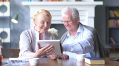 Elderly happy couple working on tablet in modern apartment Stock Footage