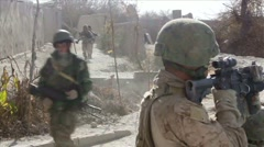 War in Afghanistan - Two soldiers cover a unit of Marines Stock Footage