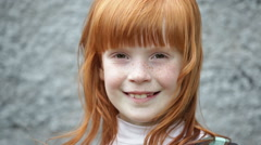 Close up little ginger girl's face  smiling, gray background outdoors - stock footage