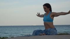 Woman practicing sukhasana warming up outdoors on the blue tropical beach Stock Footage