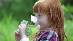 Little red-haired girl sniffing blossoming branch in the park, green backgrou - stock footage