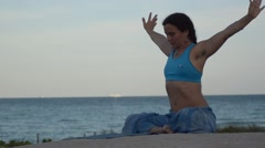 Girl practicing sukhasana warming up outdoors on the blue tropical beach Stock Footage