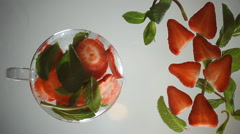 Strawberry, mint and ice on a glass surface.  Stock Footage