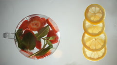 Strawberry, lemon, mint and ice on a glass surface.  Stock Footage