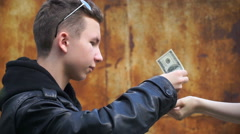 Footage rich teenager gives money to loan - stock footage