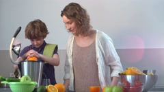 Young Caucasian Mother and Child Homemade Fresh Orange Juice in Kitchen with Stock Footage