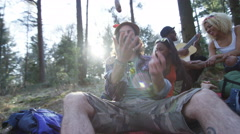 4K Happy hipster friends camping in the woods, playing guitar & singing - stock footage