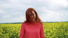 Happy red girl looking on the sky, smiling in the rape field 4k Stock Footage